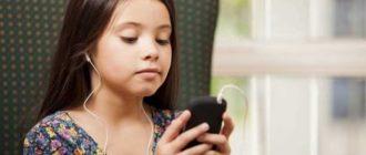 девочка смотрит в телефон и слушает
