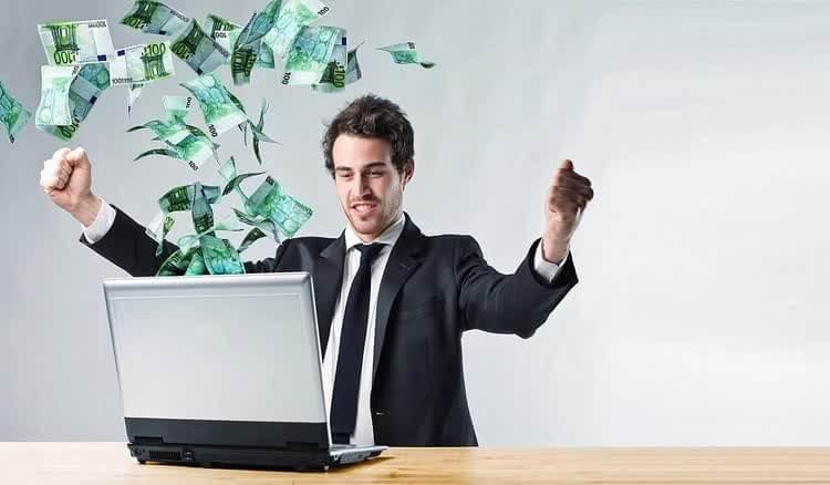 Мужчина за компьютером из которого вылетают деньги