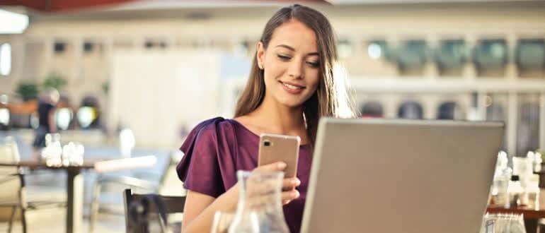 Девушка смотрит в телефон для заработка в интернете