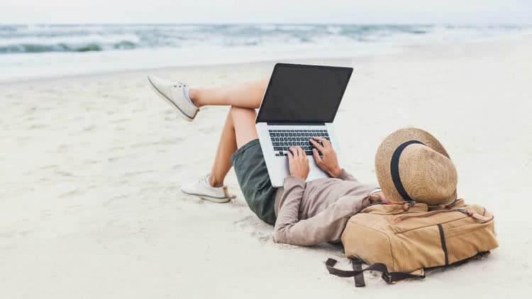 мужчина зарабатывает лежа на пляже у моря