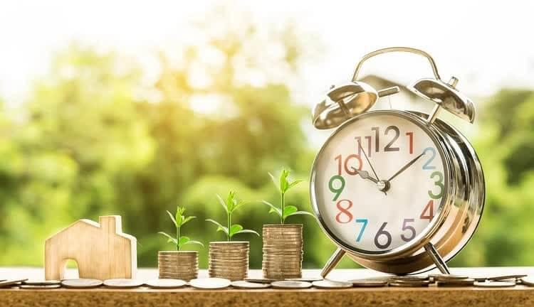 Будильник и зеленые ростки из стопок денег