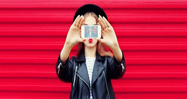 Девушка фотографирует себя на телефон