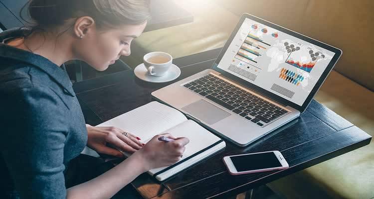 Девушка пишет в блокноте перед компьютером