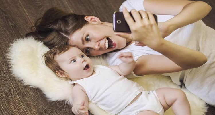 Женщина с младенцем смотрят телефон