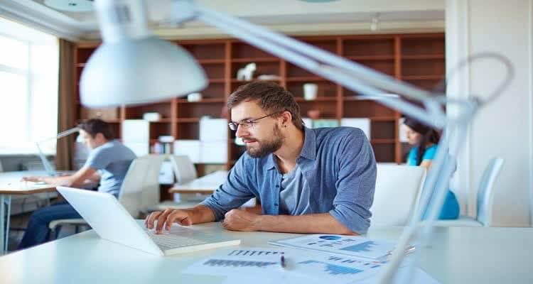 Мужчина работает за компьютером на фоне лампы