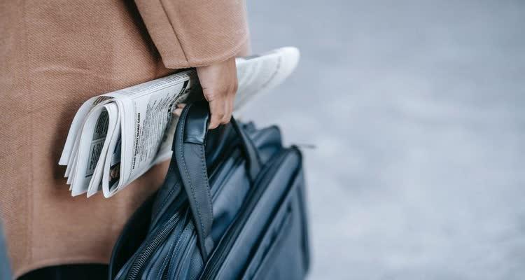 Человек с портфелем и газетой в руке