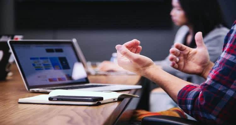 Жестикулирует руками перед ноутбуком