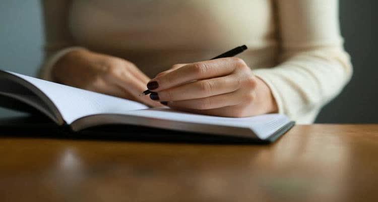 Пишет ручкой в тетраде